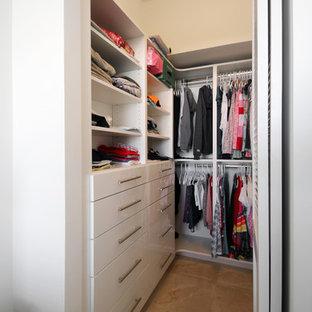 Cette photo montre un petit dressing tendance neutre avec un placard à porte plane, des portes de placard blanches, un sol en carrelage de porcelaine et un sol beige.