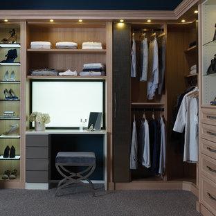 Modelo de armario vestidor de mujer, tradicional, grande, con armarios con paneles empotrados, puertas de armario de madera clara y moqueta