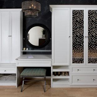 Diseño de vestidor de mujer, escandinavo, de tamaño medio, con puertas de armario blancas y suelo de madera clara