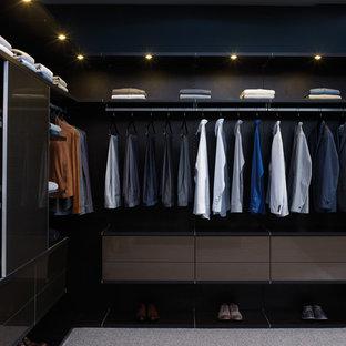 Ejemplo de armario vestidor de hombre, actual, grande, con armarios abiertos, puertas de armario negras y moqueta