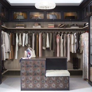 Immagine di uno spazio per vestirsi per donna shabby-chic style di medie dimensioni con ante di vetro, ante in legno bruno e moquette