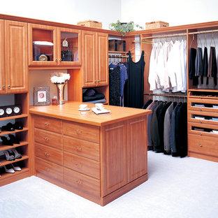 Diseño de armario vestidor unisex, tradicional, grande, con armarios con paneles con relieve, puertas de armario de madera oscura, suelo de cemento y suelo blanco