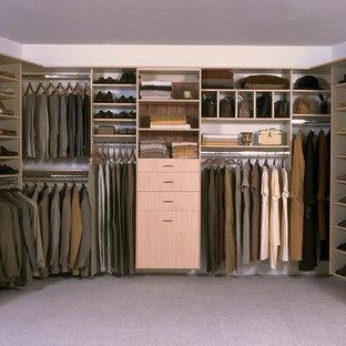 Modern inredning av ett mycket stort walk-in-closet för könsneutrala, med släta luckor, skåp i ljust trä och heltäckningsmatta