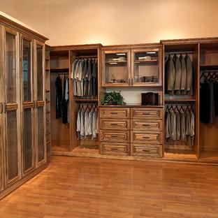 Идея дизайна: большая гардеробная комната в стиле рустика с фасадами с декоративным кантом, фасадами цвета дерева среднего тона и паркетным полом среднего тона для мужчин