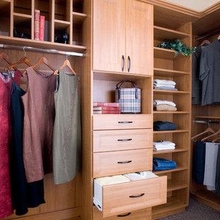 Aménagement d'un dressing classique de taille moyenne et neutre avec un placard avec porte à panneau encastré, des portes de placard en bois clair et moquette.