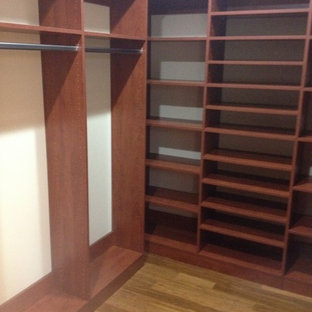 Example of a mid-sized classic gender-neutral light wood floor walk-in closet design in Other with medium tone wood cabinets and open cabinets