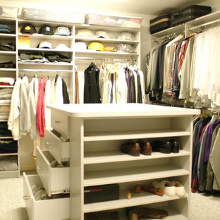 Large elegant men's carpeted walk-in closet photo in New York with open cabinets and white cabinets