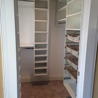 Ejemplo de armario vestidor unisex, clásico, grande, con armarios abiertos, puertas de armario blancas y suelo de baldosas de cerámica