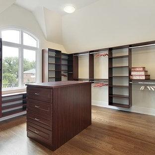 Imagen de vestidor unisex, clásico, de tamaño medio, con puertas de armario de madera en tonos medios, suelo de madera clara y armarios abiertos