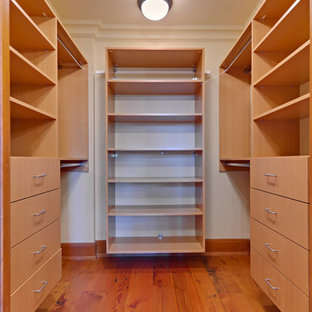 This is an example of a mid-sized transitional gender-neutral walk-in wardrobe in Cleveland with open cabinets, light wood cabinets, medium hardwood floors and brown floor.