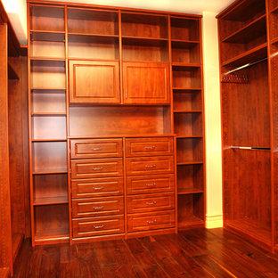 Modelo de armario vestidor unisex, tradicional renovado, grande, con armarios con paneles con relieve, suelo de madera en tonos medios y puertas de armario de madera oscura
