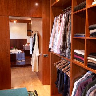 Ejemplo de armario vestidor unisex, actual, de tamaño medio, con armarios con paneles lisos, puertas de armario de madera oscura y suelo de madera clara