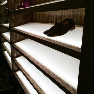 マイアミの大きい男女兼用モダンスタイルのおしゃれなウォークインクローゼット (オープンシェルフ、濃色木目調キャビネット、スレートの床) の写真