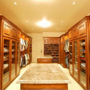 Immagine di una grande cabina armadio per uomo stile americano con ante con bugna sagomata, ante in legno scuro e pavimento con piastrelle in ceramica