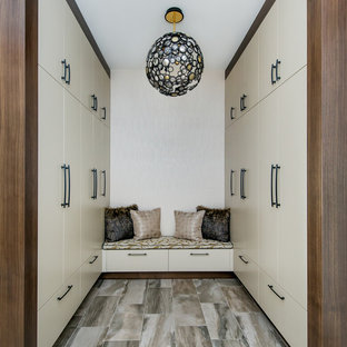 Inspiration for a mid-sized contemporary gender-neutral porcelain floor and multicolored floor walk-in closet remodel in Calgary with flat-panel cabinets and white cabinets