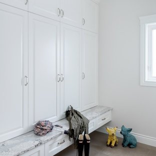 Esempio di una grande cabina armadio chic con ante con bugna sagomata, ante bianche, pavimento in gres porcellanato e pavimento beige