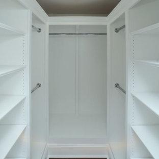 Modelo de vestidor unisex, tradicional, de tamaño medio, con armarios con paneles con relieve, puertas de armario blancas y suelo de madera oscura