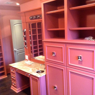 Photo of a large modern women's dressing room in New York with raised-panel cabinets, red cabinets and dark hardwood floors.