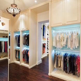 Exemple d'un très grand dressing tendance neutre avec un placard avec porte à panneau surélevé, des portes de placard blanches et un sol en vinyl.
