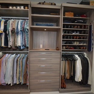 Example of a mid-sized trendy men's dressing room design in Tampa with flat-panel cabinets and medium tone wood cabinets