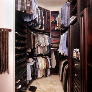 Modelo de armario vestidor de hombre, tradicional, de tamaño medio, con puertas de armario de madera en tonos medios, armarios abiertos y suelo de baldosas de porcelana