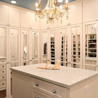 Esempio di una grande cabina armadio per donna classica con ante bianche, pavimento in legno massello medio e ante in stile shaker