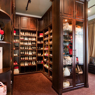 Example of a large classic women's carpeted walk-in closet design in Tampa with glass-front cabinets and dark wood cabinets