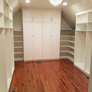 Mid-sized walk-in wardrobe in Chicago with shaker cabinets, white cabinets, medium hardwood floors and brown floor.