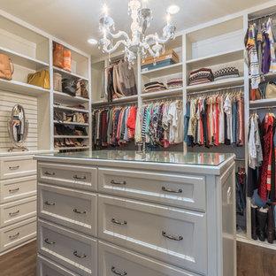 Foto på ett stort vintage omklädningsrum för kvinnor, med luckor med infälld panel, vita skåp, mörkt trägolv och brunt golv