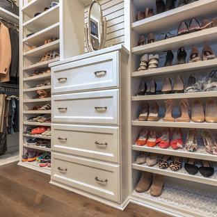 Idee per un grande spazio per vestirsi per donna tradizionale con ante con riquadro incassato, ante bianche, parquet scuro e pavimento marrone