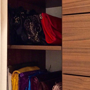 Inspiration for a mid-sized modern women's walk-in closet remodel in New York with dark wood cabinets