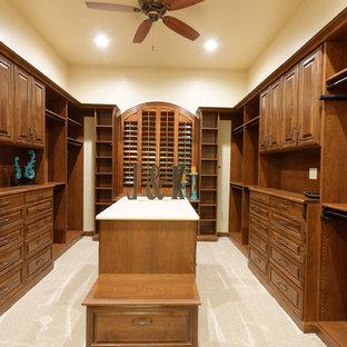 Ejemplo de armario vestidor unisex, mediterráneo, grande, con armarios con paneles con relieve, puertas de armario de madera en tonos medios, moqueta y suelo beige