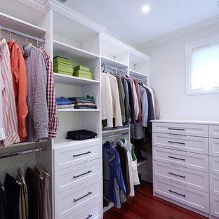Cette image montre un grand dressing craftsman neutre avec un placard à porte shaker, des portes de placard blanches, un sol en bois foncé et un sol rouge.