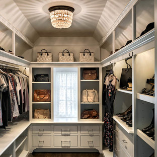 Traditional walk-in wardrobe in Boston with flat-panel cabinets, white cabinets, dark hardwood floors and brown floor.