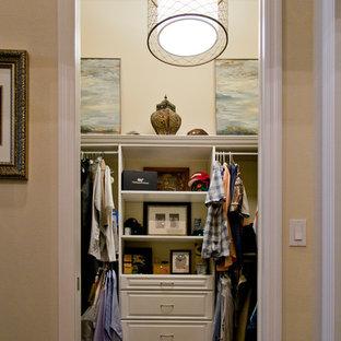 Ejemplo de armario vestidor unisex, tradicional renovado, de tamaño medio, con armarios con puertas mallorquinas, puertas de armario blancas, suelo de madera oscura y suelo marrón
