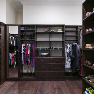 Ejemplo de armario vestidor unisex, costero, grande, con armarios abiertos, puertas de armario de madera en tonos medios, suelo de madera oscura y suelo marrón