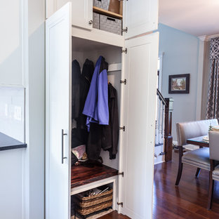 Modelo de armario unisex, clásico renovado, de tamaño medio, con armarios con paneles empotrados, puertas de armario blancas, suelo de madera en tonos medios y suelo marrón