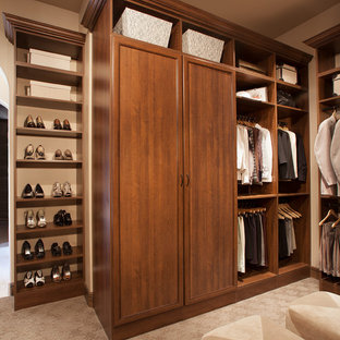 Traditional gender-neutral walk-in wardrobe in Orange County with flat-panel cabinets, medium wood cabinets and carpet.