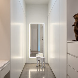 Inspiration for a modern gender-neutral dressing room in Seattle with flat-panel cabinets, white cabinets, concrete floors and grey floor.