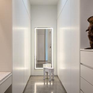 Immagine di uno spazio per vestirsi unisex moderno con ante lisce, ante bianche, pavimento in cemento e pavimento grigio