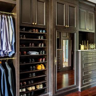 Idées déco pour un grand dressing classique pour un homme avec des portes de placard en bois sombre, un sol en bois brun et un placard avec porte à panneau encastré.