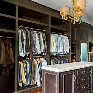 Imagen de armario vestidor de hombre, tradicional, grande, con puertas de armario de madera en tonos medios, suelo de madera en tonos medios y armarios con paneles empotrados