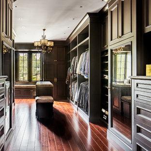 Esempio di una grande cabina armadio per uomo chic con ante in legno bruno, ante con riquadro incassato e pavimento in legno massello medio