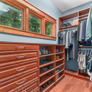 Diseño de armario vestidor de hombre, de estilo americano, de tamaño medio, con armarios con paneles con relieve, puertas de armario de madera oscura, suelo de madera en tonos medios y suelo marrón