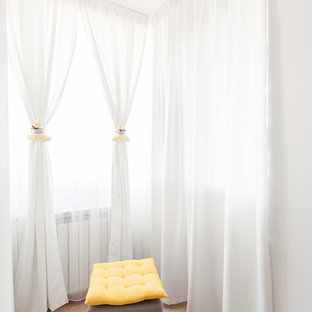 Immagine di un piccolo spazio per vestirsi unisex minimal con nessun'anta, ante bianche e pavimento in compensato