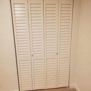 Immagine di un piccolo armadio o armadio a muro moderno con parquet chiaro e pavimento multicolore