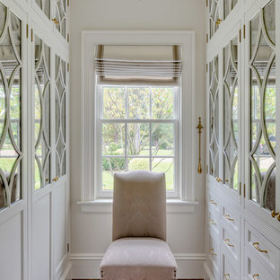 Example of a mid-sized farmhouse gender-neutral brown floor and dark wood floor walk-in closet design in Boston with recessed-panel cabinets and white cabinets
