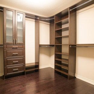 Aménagement d'un dressing contemporain de taille moyenne et neutre avec un placard avec porte à panneau surélevé, des portes de placard marrons et un sol en bois foncé.