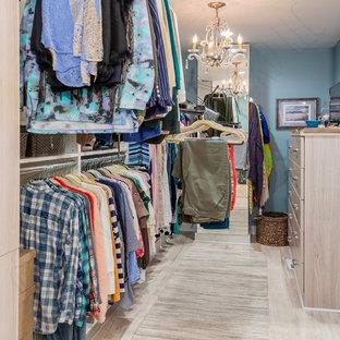 Imagen de vestidor unisex, tradicional renovado, de tamaño medio, con armarios con paneles lisos, puertas de armario de madera clara, suelo de piedra caliza y suelo beige