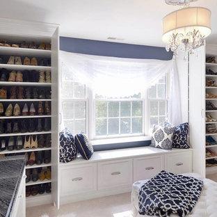 フィラデルフィアの広い女性用シャビーシック調のおしゃれなウォークインクローゼット (レイズドパネル扉のキャビネット、白いキャビネット、カーペット敷き、ベージュの床) の写真